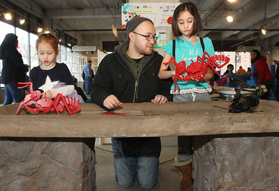 Candace H. Johnson-For Shaw Media Wilson Avila, of Waukegan (center) kneels as he helps his daughters, Emmilia, 6, and Asia, 9, build toy ants at the Kohl Children's Museum pop-up museum at the Urban Edge storefront gallery on Clayton Street in downtown Waukegan. The pop-up museum will be open until March 23rd. (2/16/19)