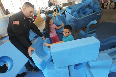 Candace H. Johnson-For Shaw Media Marco Vazquez, a Lieutenant with the Waukegan Fire Department, stops by with other firefighters to lend a hand as Crystal Gonzalez, 5, and her brother, Jonathan, 10, build a tower in the Imagination Playground at the Kohl Children's Museum pop-up museum at the Urban Edge storefront gallery on Clayton Street in downtown Waukegan. The pop-up museum will be open until March 23rd. (2/16/19)