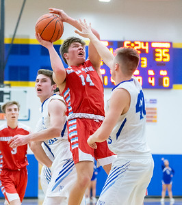 Marian Central Catholic's Austin Geils fights to get a shot off over Woodstock's Ethan Patterson Monday, February 25, 2019 at Class 3A Boys Basketball Regional held at Johnsburg High School in Johnsburg. Marian went on to get their second win of the year beating Woodstock 75-68 and will face Johnsburg tomorrow night. KKoontz – For Shaw Media