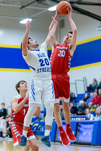 Marian Central Catholic's Brogan Pivnicka goes up for the shot over Woodstock's David Shinherr Monday, February 25, 2019 at Class 3A Boys Basketball Regional held at Johnsburg High School in Johnsburg. Marian went on to get their second win of the year beating Woodstock 75-68. KKoontz – For Shaw Media