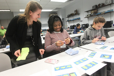 Candace H. Johnson-For Shaw Media Michelle Leonard, of Mundelein, chair of electrical engineering technology, teaches Lavender Griffin, 13, of Gurnee and Anna Becker, 14, of Green Oaks how to make paper circuit light-up hopping frogs during STEM for Girls at the College of Lake County in Grayslake. STEM stands for Science, Technology, Engineering and Math. (2/23/19)