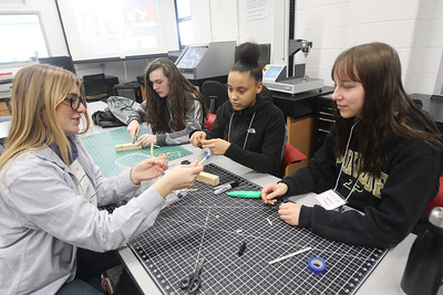 Candace H. Johnson-For Shaw Media Neoneela Boevets, of Mundelein, a volunteer second-year student, helps Katherine Cheh, 15, of Barrington, Nyanna Stinnette, 14, of Beach Park and Aubrey Tabor, 14, of Barrington make fingers for a prosthetic hand in the Fab Lab during STEM for Girls at the College of Lake County in Grayslake. STEM stands for Science, Technology, Engineering and Math. (2/23/19)