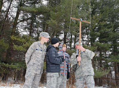 """From left: Capt. Elizabeth Genengels, Cadet Tyler Genengels, and Cadet Hunter Seymour, all of McHenry, receive instruction from Col. Bob Tyler of Elgin on how to use an """"L-per"""" direction finder to locate a search beacon during the Civil Air Patrol (CAP) Ice Bowl 2020, a cold-weather search and rescue training exercise held by the Illinois Wing of the CAP on Saturday, February 1, 2020 in Gilberts, IL."""
