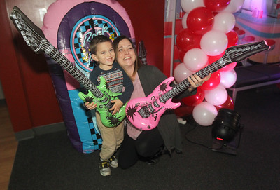 Candace H. Johnson-For Shaw Media Harrison Paquette, 3, of Fox Lake and his mother, Heather, get their photo taken as they hold inflatable guitars during the Sock Hop Mother & Son dance at the Lakefront Park Building in Fox Lake. (2/1/20)