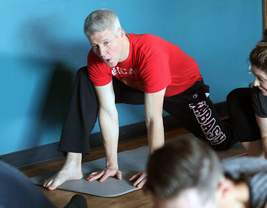 Candace H. Johnson-For Shaw Media Mike Hawksworth, of Gurnee holds a yoga pose during Poses and Pints in the taproom at the Tighthead Brewing Company in Mundelein. The yoga class is held at the brewery on the first Sunday of every month at 10:30 am. (2/2/20)