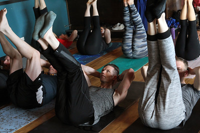 Candace H. Johnson-For Shaw Media Jim Kalcsits, of Prospect Heights (center) works on his core strength during Poses and Pints in the taproom at the Tighthead Brewing Company in Mundelein. The yoga class is held at the brewery on the first Sunday of every month at 10:30 am. (2/2/20)