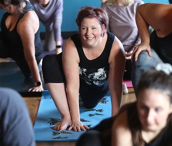 Candace H. Johnson-For Shaw Media Stacey Cronin, of Mundelein holds a yoga pose during Poses and Pints in the taproom at the Tighthead Brewing Company in Mundelein. The yoga class is held at the brewery on the first Sunday of every month at 10:30 am. (2/2/20)