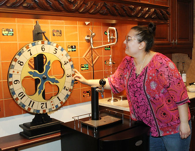 Candace H. Johnson-For Shaw Media Laura Frye, of Waukegan, tasting room associate, spins the Wheel of Indecision, to help customers decide what they want to drink, in the Tasting Room at North Shore Distillery in Green Oaks. (2/8/20)