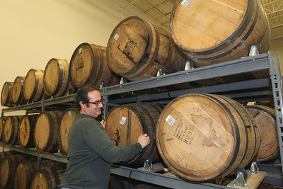 Candace H. Johnson-For Shaw Media Derek Kassebaum, co-owner, turns his barrels of rum at North Shore Distillery in Green Oaks. Kassebaum owns the distillery with his wife, Sonja. (2/8/20)