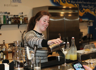 Candace H. Johnson-For Shaw Media Bartender Caroline Ruedig, of Libertyville makes a drink called a New Orleans Fizz for a customer at the bar in the Tasting Room at the North Shore Distillery in Green Oaks. (2/8/20)