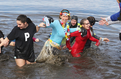 Candace H. Johnson-For Shaw Media Sarah Emerson, Cory Knopik and Serenity Boxlietner with the Punny Plungers team from Woodstock School District 200 run through the frigid water during the Fox Lake Polar Plunge at Lakefront Park in Fox Lake. The event was presented by the Law Enforcement Torch Run to support Special Olympics Illinois. (2/16/20)