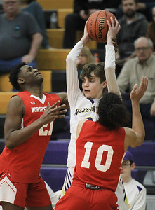 Candace H. Johnson-For Shaw Media Wauconda's Justin Drobnik looks to pass against North Chicago's Nasir Zakai Young and Jericoe Johnson in the fourth quarter at Wauconda High School. Wauconda won 67-58. (2/18/20)