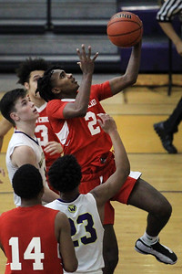 Candace H. Johnson-For Shaw Media North Chicago's Jamar Mays leaps up for a shot against Wauconda's Nicholas Bulgarelli and Donovan Carter in the third quarter at Wauconda High School. Wauconda won 67-58. (2/18/20)