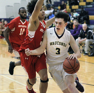 Candace H. Johnson-For Shaw Media Wauconda's Nicholas Bulgarelli drives to the hoop against North Chicago's Javonta Beech in the fourth quarter at Wauconda High School. Wauconda won 67-58. (2/18/20)