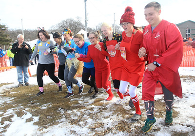 Candace H. Johnson-For Shaw Media The Punny Plungers team with Woodstock School District 200 runs towards the frigid water during the Fox Lake Polar Plunge at Lakefront Park in Fox Lake. The event was presented by the Law Enforcement Torch Run to support Special Olympics Illinois. (2/16/20)