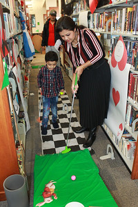 Candace H. Johnson-For Shaw Media Adi Basu, 5, of Grayslake plays mini golf with his parents, Debolina, and Atish, during the Grayslake Library Foundation's 9th Annual MiniGolf Fundraiser at the Grayslake Area Public Library. (2/22/20)