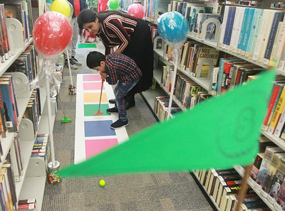 Candace H. Johnson-For Shaw Media Adi Basu, 5, of Grayslake plays mini golf with his mother, Debolina, during the Grayslake Library Foundation's 9th Annual MiniGolf Fundraiser at the Grayslake Area Public Library. Adi's father, Atish, was also at the library's fundraiser. (2/22/20)