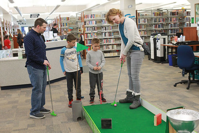 Candace H. Johnson-For Shaw Media Travis and Alissa Brown, both of Grayslake play mini golf with their children, M.J., 8, and Luke, 6, at the 12th Hole during the Grayslake Library Foundation's 9th Annual MiniGolf Fundraiser at the Grayslake Area Public Library. (2/22/20)