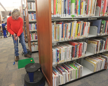 Candace H. Johnson-For Shaw Media Beverly Young, of Grayslake plays mini golf in-between the book shelves during the Grayslake Library Foundation's 9th Annual MiniGolf Fundraiser at the Grayslake Area Public Library.Young was at the library with her granddaughter, Simone Albert, 6, of Grayslake. (2/22/20)