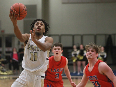 Candace H. Johnson-For Shaw Media Grayslake North's Tony Hines leaps up for a shot against Lakes Jake Sanders and Tylor Gunther in the first quarter at Grayslake North High School. Grayslake North won 64-54. (2/25/20)