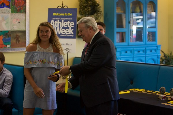 Geneva basketball player Stephanie Hart accepts her medal from Tom Hansen at the 2017 Kane County Chronicle Athlete of the Week Awards Banquet on June 7 at Abby's in St. Charles.