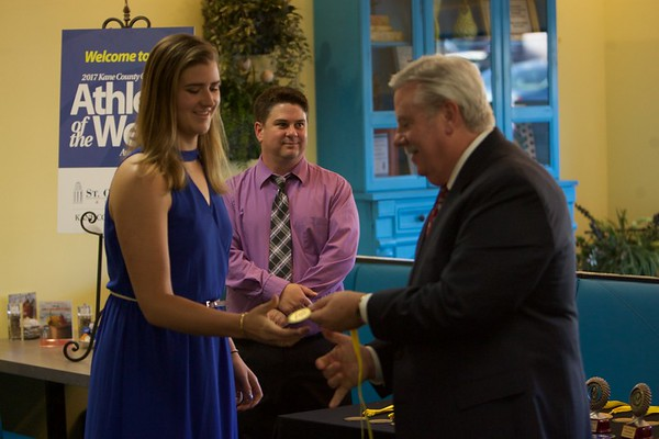 Geneva volleyball player Allyson Barrett accepts her medal from Tom Hansen at the 2017 Kane County Chronicle Athlete of the Week Awards Banquet on June 7 at Abby's in St. Charles.