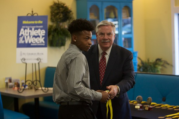 Batavia football player Reggie Phillips accepts his medal from Tom Hansen at the 2017 Kane County Chronicle Athlete of the Week Awards Banquet on June 7 at Abby's in St. Charles.