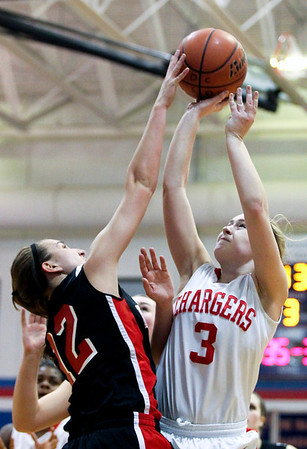 Jenny Kane - jkane@shawmedia.com Tues. Jan. 3, 2012, Dundee-Crown's Carlin Faulkner tries to take a shot as Huntley's Haley Ream blocks the shot during the third period. Dundee-Crown defeated Huntley 44-41 at Dundee.