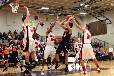 Lauren M. Anderson - landerson@shawmedia.com Swarmed by Huntley players Crystal Lake Central's Chase Cane attempts to put up a shot in the fourth quarter during Wednesday's game.