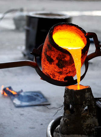 Sarah Nader - snader@shawmedia.com Sculptor Erik Blome of Crystal Lake pours molten bronze into a mold while working at his studio in Lake in the Hills on Thursday, January 5, 2011. Blome is working on a piece for ComEd that will go in front of its county headquarters in Crystal Lake. The statue features two linemen on a 9-foot telephone pole and a base which includes the Raue Center and Palmer House.
