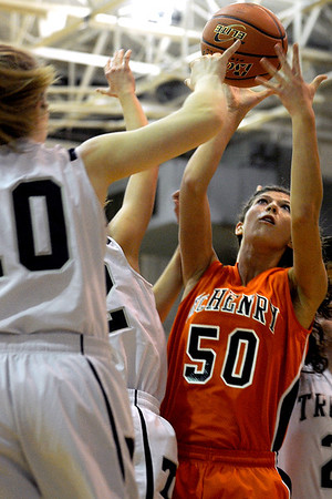 Sarah Nader - snader@shawmedia.com McHenry's Brittany Avonts (right) is guarded by Cary-Grove players while she takes a shot during the third quarter of Friday's game in Cary on January 6, 2012. Cary-Grove won, 39-18.