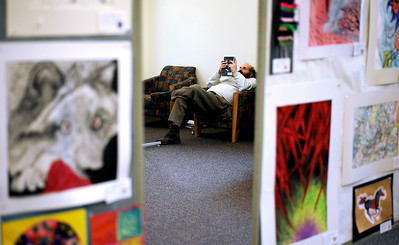 Sarah Nader - snader@shawmedia.com A man reads a book while surrounded by art from the District 200 Student Art Show at the Woodstock Public Library on Friday, January 6, 2012.