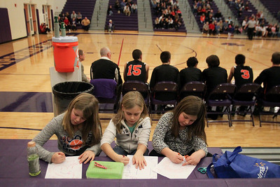 Lauren M. Anderson – landerson@shawmedia.com Alyssa Cork, 9, (left-right) Allie Dalby, 9,  and Katie Wians, 9, pay no attention to th boys basketball game behind them as they color in the stands on Thursday at Hampshire High School.