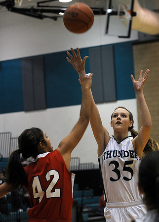 Sarah Nader - snader@shawmedia.com Rockford East's Nicole Gould (left) jumps to block a shot  by Woodstock North's Sami Ahr during the first quarter of Monday's non-confrence game in Woodstock on January, 9, 2012. Woodstock North won, 48-19.