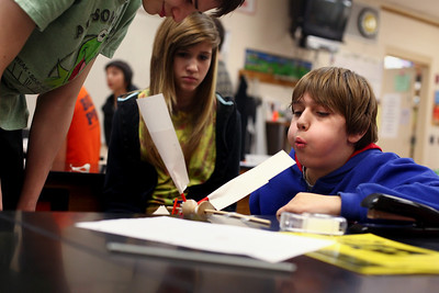 Lauren M. Anderson - landerson@shawmedia.com Robert Birkhoff, 14, (left) and Emma Costin, 13,(center) watch teammate Raymond Sikula, 13, test their wind turbine by blowing on it Wednesday during Engineering Week at Hannah Beardsley Middle School.