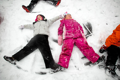 Jenny Kane - jkane@shawmedia.com Thurs. Jan. 12, 2012, Lily Rymsza, (left) and Maya Helzer, (right) make snow angels with other children from the four year olds classroom at St. Barnabas Christian Preschool in Cary. The children played in the snow as a reward at the end of their school day. It was the first snow of the year.