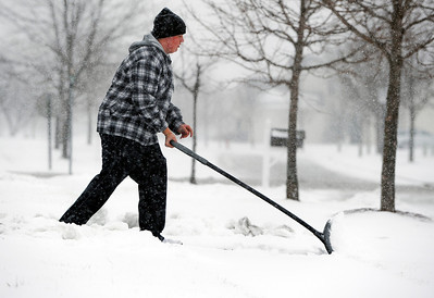 Sarah Nader - snader@shawmedia.com Jason Garcia, 14, of Huntley shovels his driveway on Great Planes Court during the first snow fall of the year on Thursday, January 12, 2012.