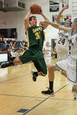 Lauren M. Anderson - landerson@shawmedia.com Crystal Lake South's Nick Geske (32) puts up a jumper in the second quarter against Cary-Grove's Jake Bianchi (24) and Zach Taylor (2) on Friday during their FVC Valley matchup. The Gators defeated the Trojans 48-44.