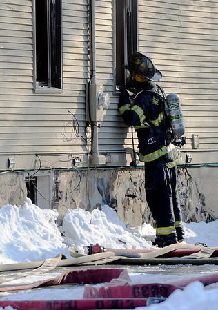 Sarah Nader - snader@shawmedia.com A Woodstock firefighter works to put out a fire that occurred in the afternoon on Sunday, January 15, 2012 at 430 E Calhoun Street in Woodstock.