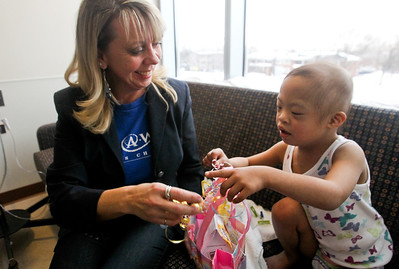 Lauren M. Anderson - landerson@shawmedia.com Chrissy Callaway gives a present to Gabriel Guzon, 4, Hoffman Estates on Monday at Advocate Lutheran General Hospital in Park Ridge. Callaway has been visiting the four-year-old leukemia patient as part of the Make-A-Wish Foundation. Callaway is a wish granter for the organization and is involved with granting Guzon's wish of visiting Disney World.