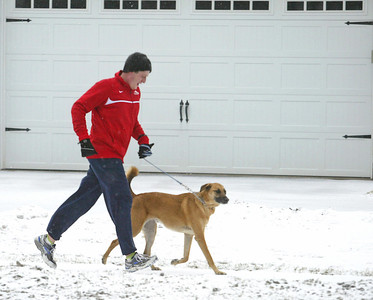 H. Rick Bamman -hbamman@shawmedia.com Justin Dusek and Smokey wrap up their four mile run in the snow along Dole Avenue in Crystal Lake Tuesday morning.