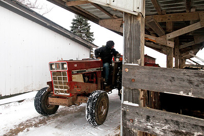Lauren M. Anderson - landerson@shawmedia.com David Vanderstappen, a dairy and cattle farmer on his family-owned farm in Hebron, lays down feed for his cows on Tuesday. Despite the winter weather Vanderstappen keeps his work schedule the same as in the summer months. (1/17/2012)