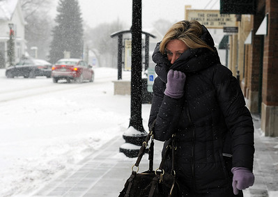 Sarah Nader - snader@shawmedia.com Susie Fox of Crystal Lake bundles up in the snow while picking up lunch on W Williams Street in Downtown Crystal Lake on Friday, January 20, 2012. Accumulations as high as eight inches are predicted, with the deepest snow expected to fall along the Illinois-Wisconsin border.