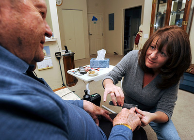 Sarah Nader - snader@shawmedia.com Conrad Larson's daughter, Chris Stephan (right) clips his nails while visiting Larson at the Spring Meadows Assisted Living Retirement Community in Libertyville on Friday, January 20, 2012. Stephan spends the night at her fathers home several times a week so she can take care of all of his needs.