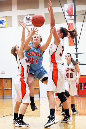 Lauren M. Anderson - landerson@shawmedia.com Marian Central's Shannon Wuensch (center) attempts to put up a shot between McHenry defenders Emma Romme (left) and Meghan Mortell in the first quarter on Thursday.