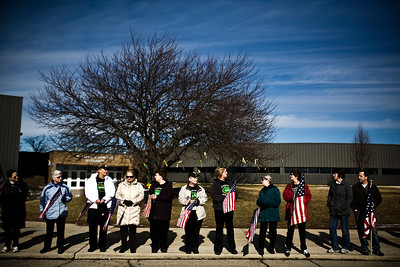 Lance Booth - lbooth@shawmedia.com School staff of Crystal Lake South waves flags in support of Marine Capt. Nathan McHone, whose body was returned to Crystal Lake today. McHone was killed in a helicopter crash in Afghanistan and was a 2011 graduate of South.