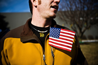 Lance Booth - lbooth@shawmedia.com A man at Crystal Lake South keeps a flag in his pocket in support of Marine Capt. Nathan McHone, whose body was returned to Crystal Lake today. McHone was killed in a helicopter crash in Afghanistan and was a 2011 graduate of South.