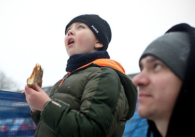 Josh Peckler - Jpeckler@shawmedia.com Jacob Wilk, 5 of Algonquin takes a break from eating pizza as he watches a skier jump during the Norge International Ski Jumping Tournament at the Norge Ski Club in Fox River Grove Sunday, January 27, 2013.