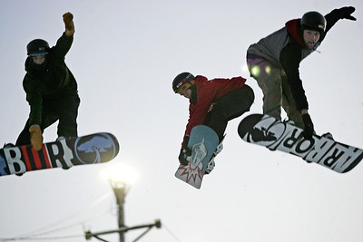 Monica Maschak - mmaschak@shawmedia.com Wade Coll (left) and Kristopher Coll (right) do a mute grab as Cooper Slack (center) does a tindy grab simulatneously off a jump at the Raging Buffalo Snowboard and Ski Park in Algonquin on Wednesday, January 2, 2013. The park offers equipment rentals as well as group and private snowboarding lessons.
