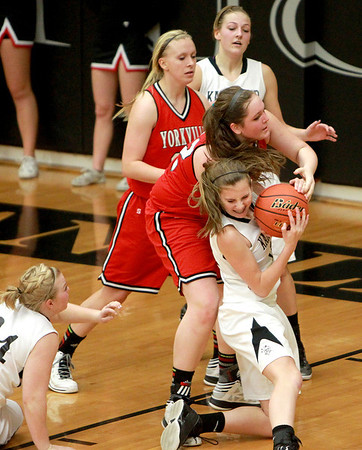 Kaneland's Vanessa Gould (center) struggles for the ball during their 26-39 loss to Yorkville Friday night.